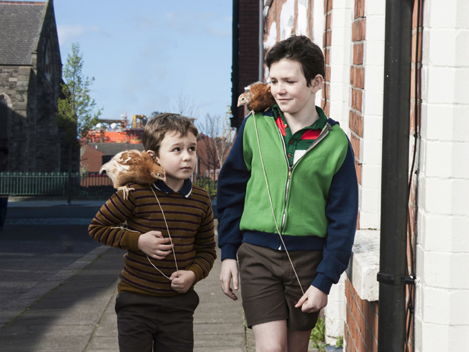 film still of two young boys walking with birds on their shoulders