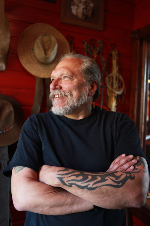 a portrait of jorma kaukonen with his arms crossed
