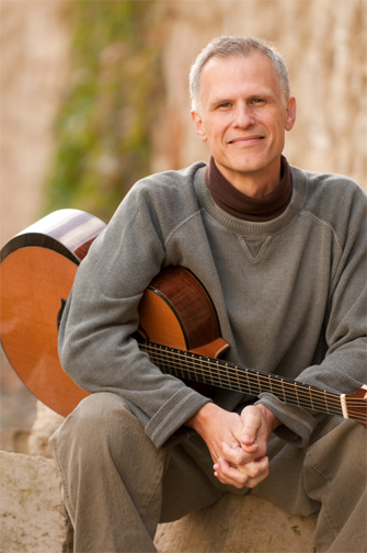 a gray haired man with a gray sweater sitting on a ledge, his hand clasped and a guitar nestled under his right armpit