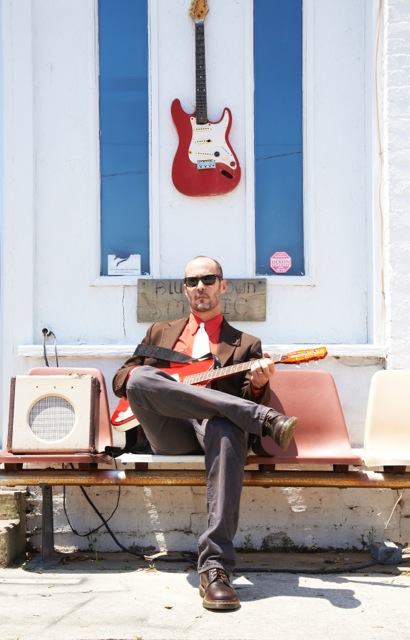 portrait of Paul Thorn seated with a guitar, an amp at his side, and another guitar hanging on the wall above him