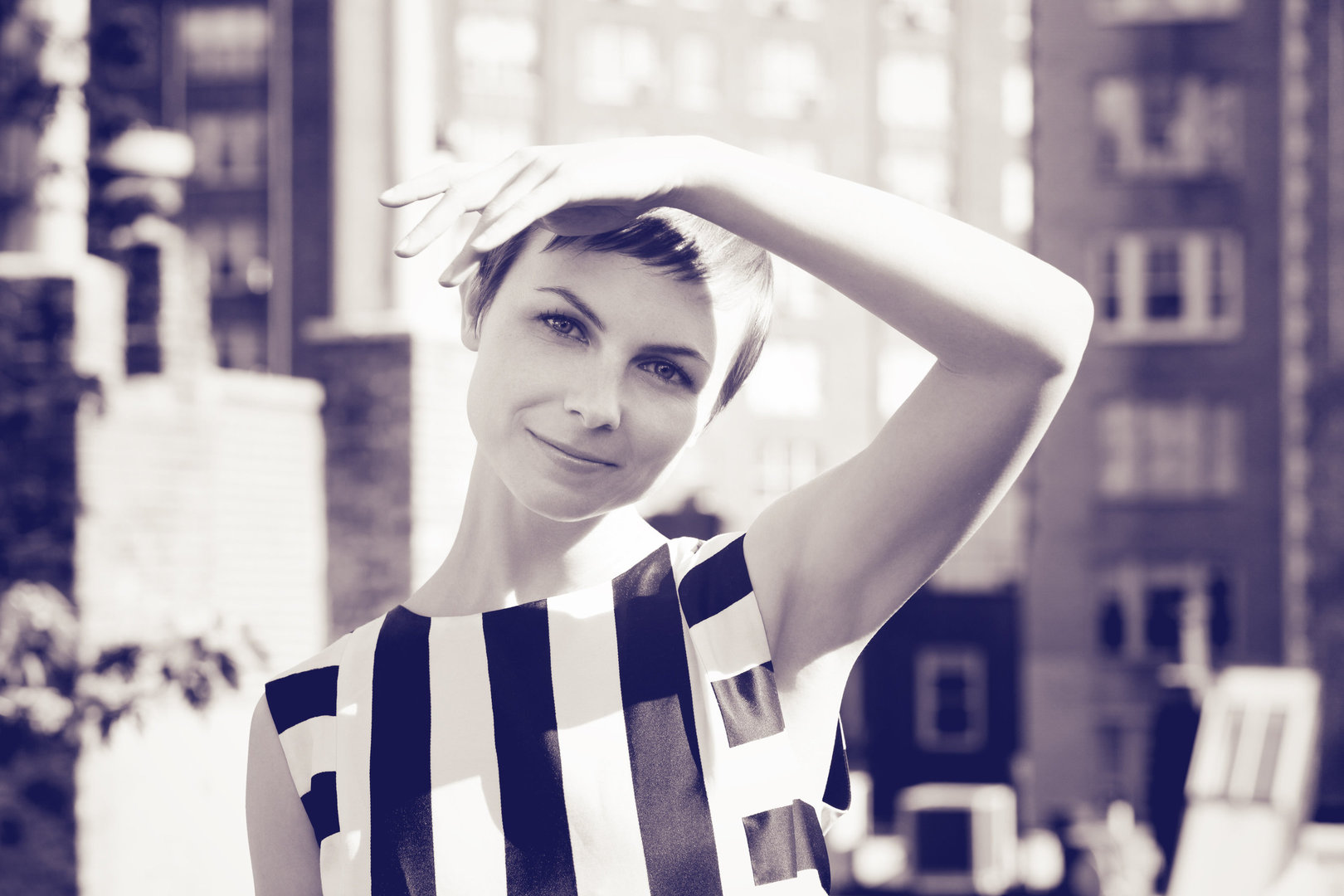 A portrait of Kat Edmonson, her left hand on her head. She has light hair in a pixie haircut, and a striped dress