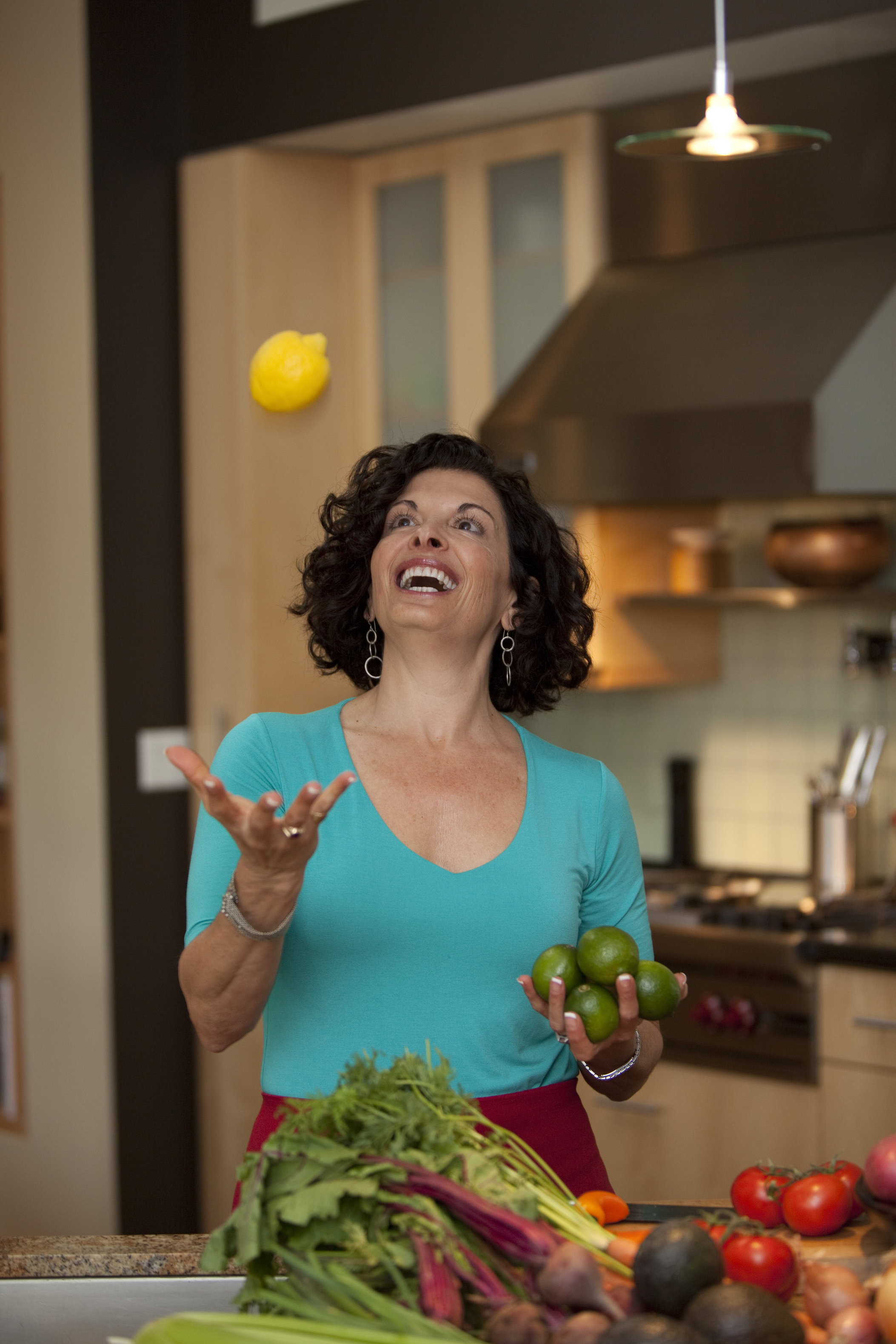 a woman tossing a lemon into the air in a kitchen setting, she is joyful
