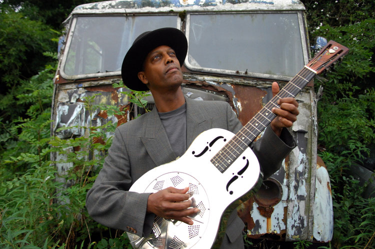 portrait of Eric Bibb with a steel guitar
