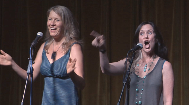 image of two women, Nina Rolle & Johanna Walker, performing on stage at microphones