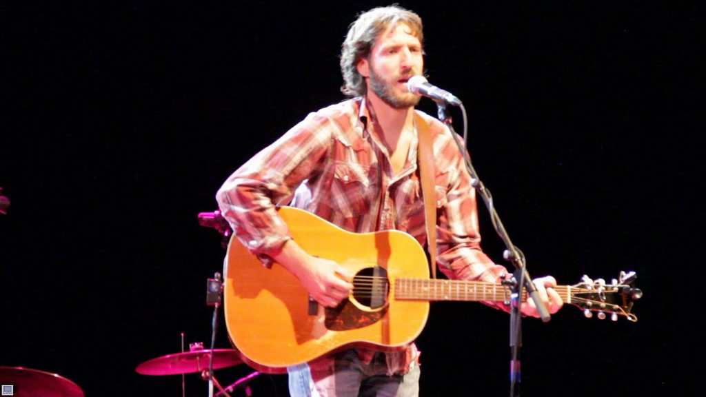 Todd Adelman stands on a stage playing a guitar, standing at a mic