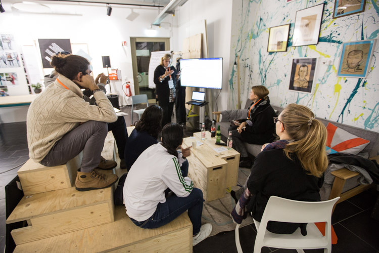 Eine kleine Gruppe Menschen unterhält sich in einem Atelier.