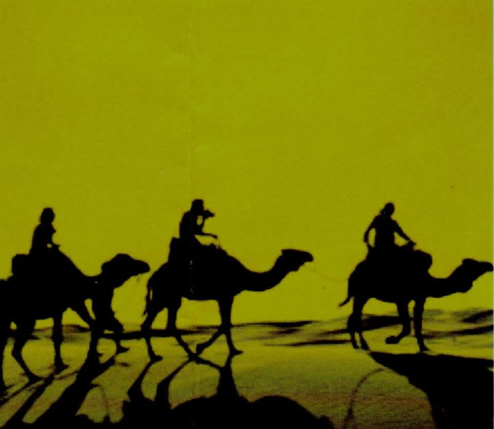 Silhouette is the image of three people riding camels through desert