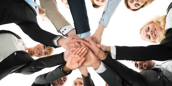 Business people joining hands in unity and teamwork