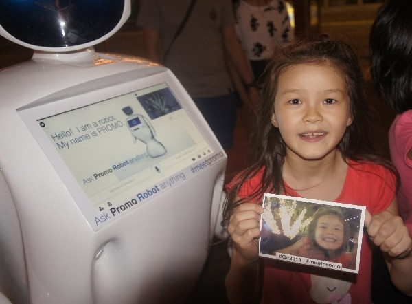 Promobot with girl printing photo