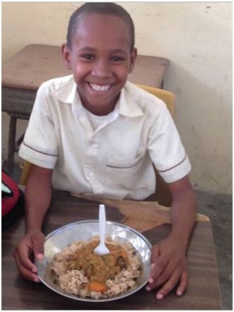 Haitian boy eating lunch