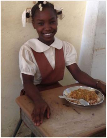 Haitian girl eating lunch