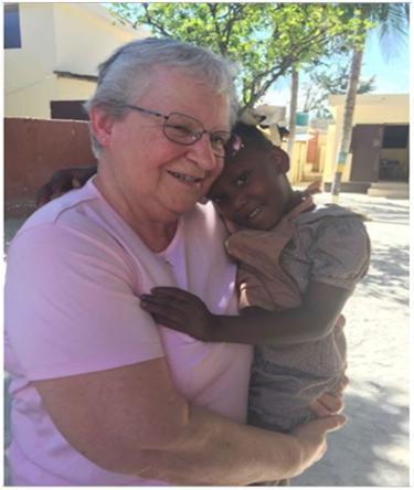 Marguerite & Haitian child hugging
