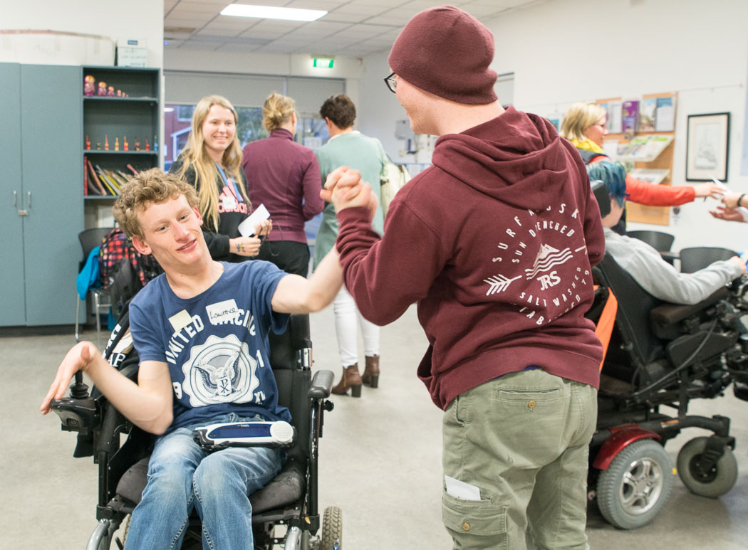 The photo shows two young men shaking hands in the foreground. One of the young men is wearing a maroon coloured jumper and beanie. The other young man is in a wheelchair and is wearing a blue t-shirt; he is smiling. There are other people in the background including a young woman who has blonde hair and is smiling.