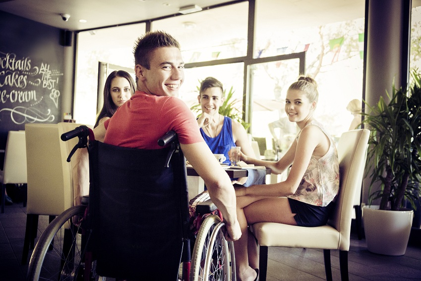Four young people sitting at a table in a cafe. One of them is in a wheelchair and wearing a red t-shirt. All of them are smiling.
