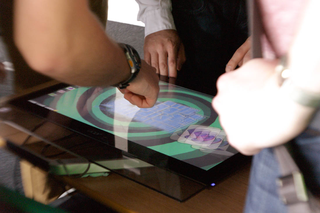 Hands playing a multiplayer touch-screen video game