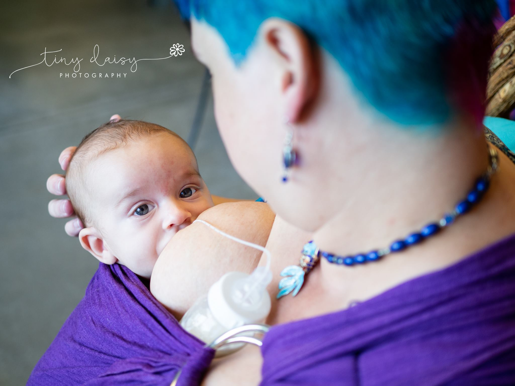 A caregiver with blue hair is tube feeding her child in a purple ring sling.