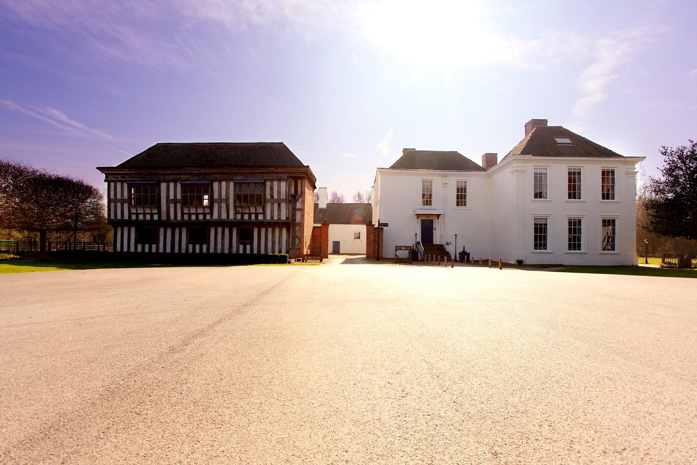 Front Facade of Middleton Hall with the Tudor timber framed Jettied building on the left and the Tudor Great Hall, now covered in white Georgian render, on the left