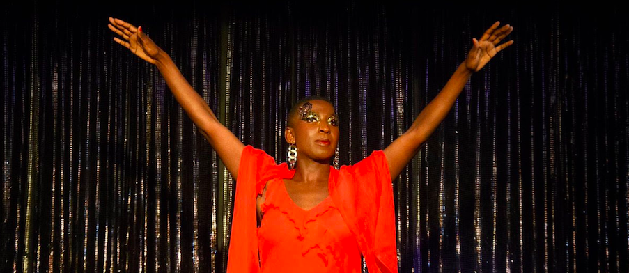 Photo of Ebony Rose Dark on a stage. She wears a flowy bright orange dress and strong glitter eyeshadow. Her arms are raised up in the air to form the letter Y in front of a silver curtain.