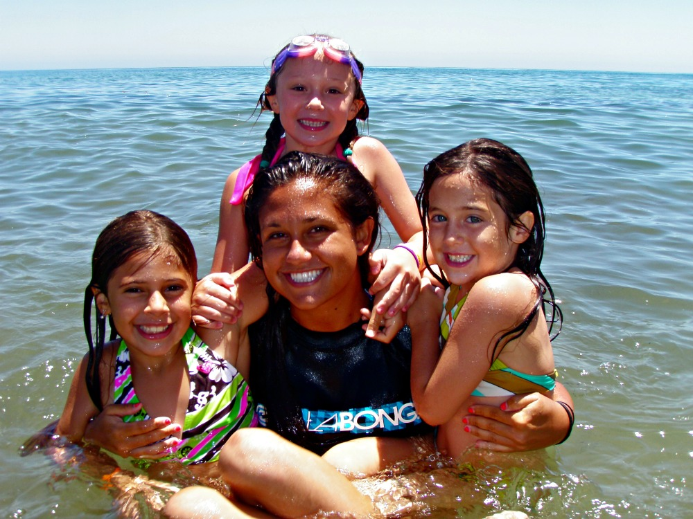 Camp counselor in the ocean with three female campers