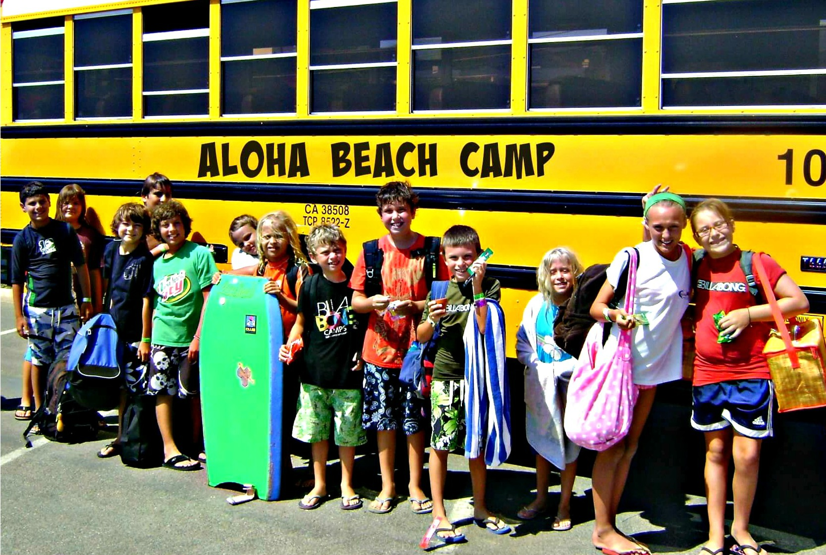 Campers standing in front of an Aloha Beach Camp Summer Day Camp bus.