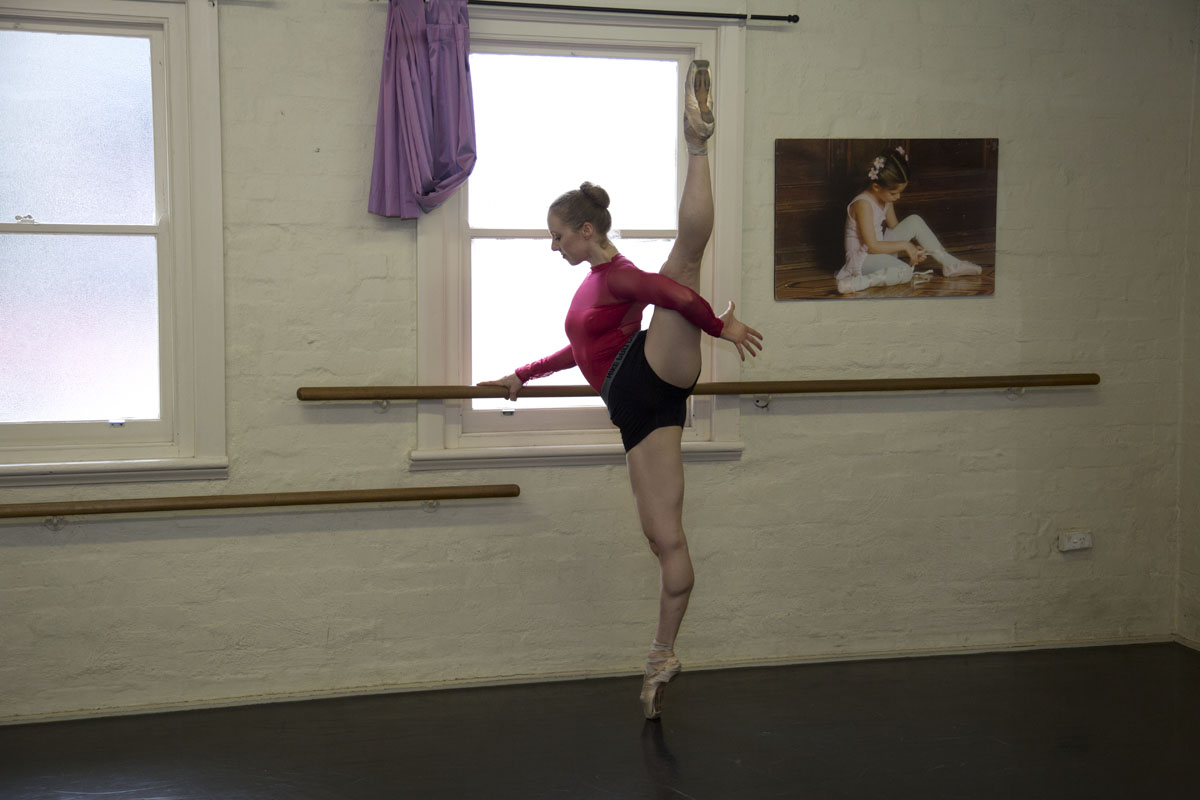 Briar Adams stretching at the barre with the leg in a la seconde