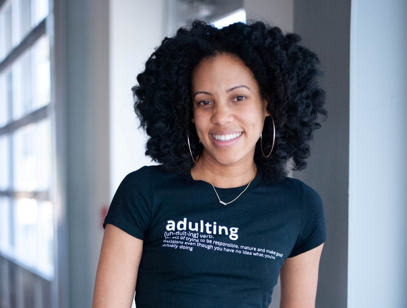 Young black woman smiles in t-shirt that says 'Adulting'