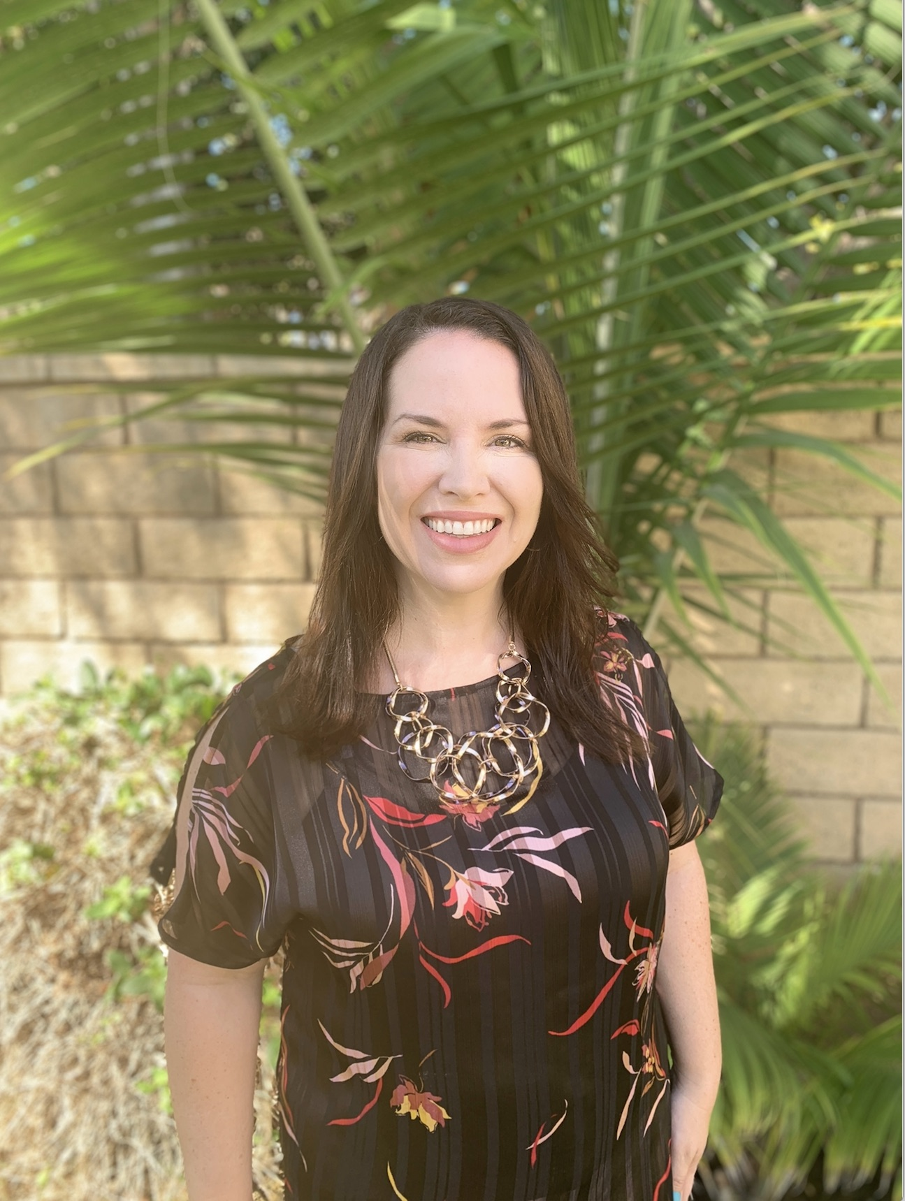 Headshot of Dr. Edlyn Peña, smiling in a black floral dress, standing in front of a  palm tree.