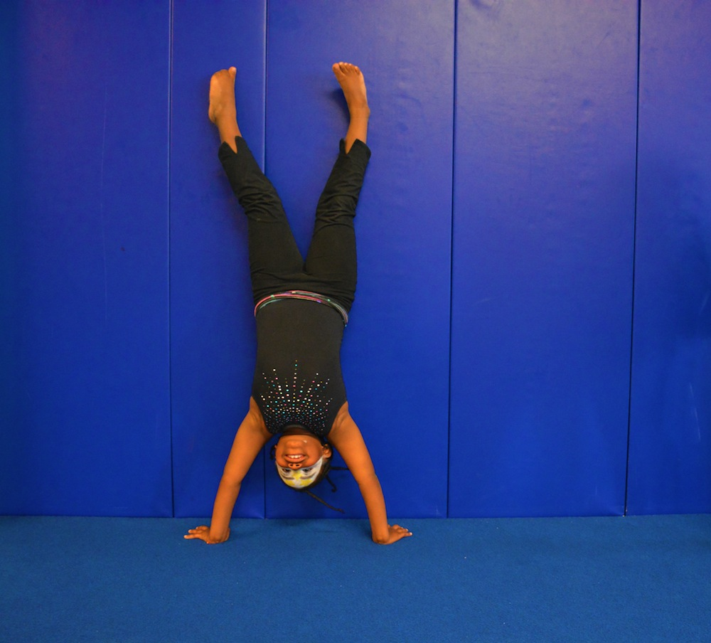Youth program participant doing a handstand