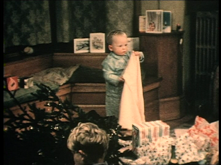 Image of child amongst open christmas presents and wrappings