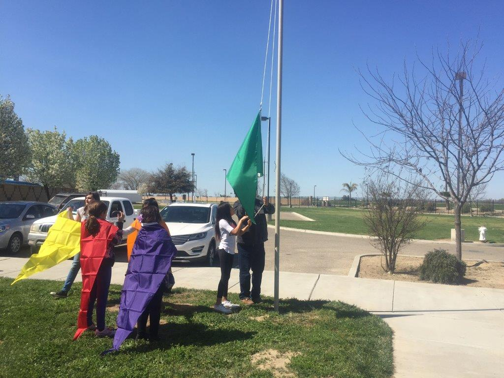 Members of the Tachi Yokut tribe raise the air quality flag in Lemoore, CA.