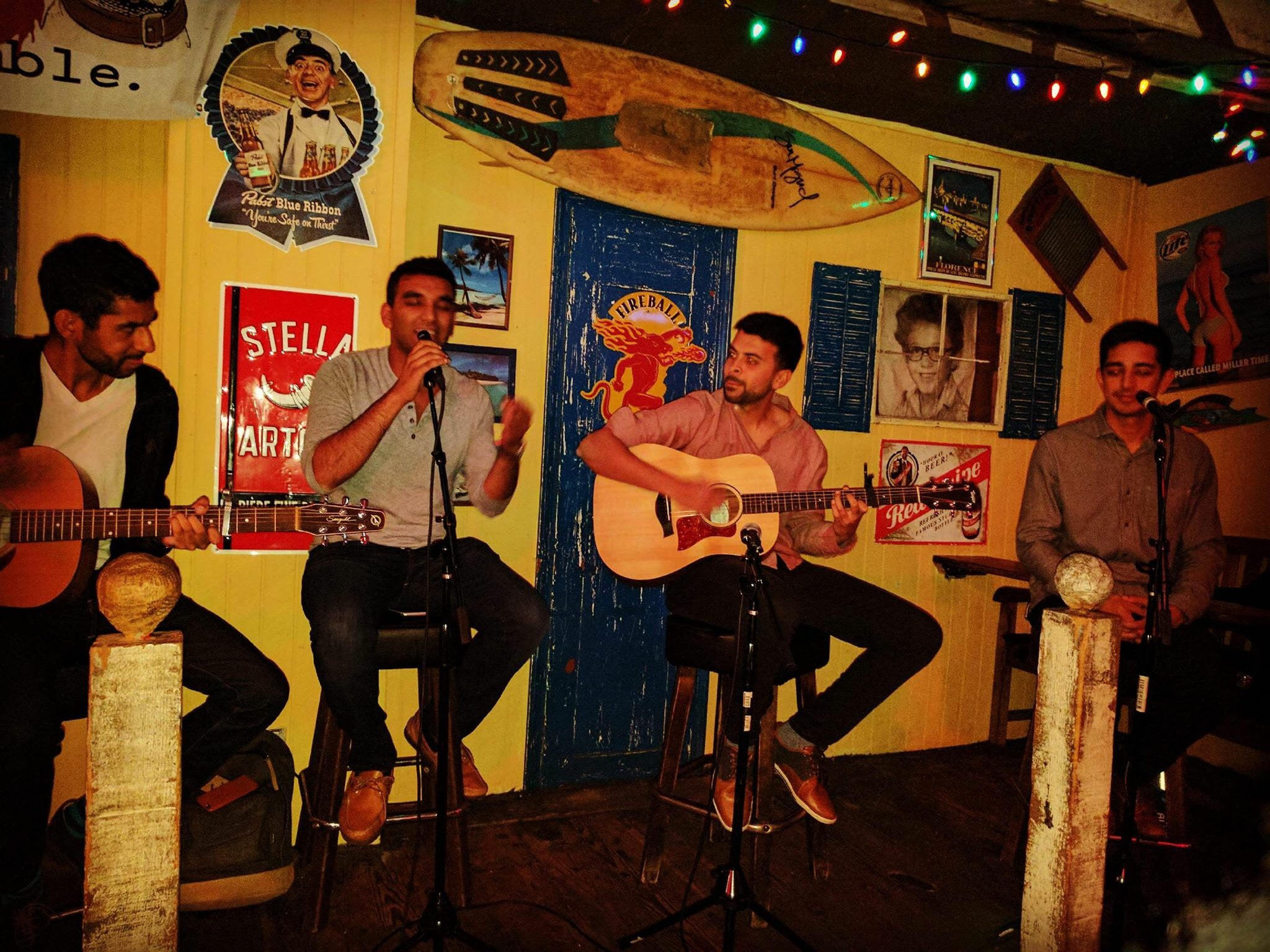 4 young men sitting on stools with one singing into a microphone and 2 holding guitars. There are street signs hanging on the back wall.