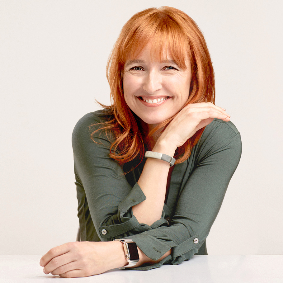 Melinda has red hair and is wearing a forest green top. Her right arm is on her left shoulder and her left arm is resting on a table in front of her.
