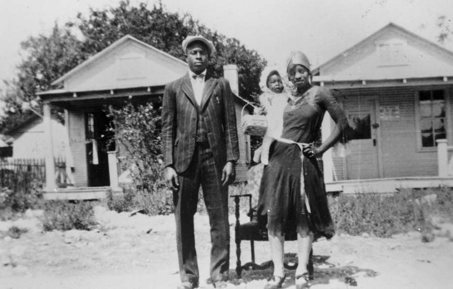 Couple in front of their home in the Baptist Settlement