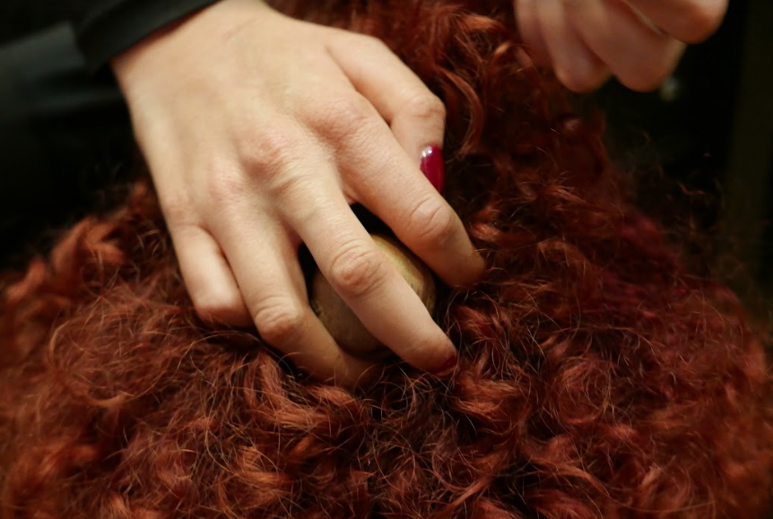 Close up hand with deep red painted nails softly holding and moving small palm sized brass ball through bright red Afro-Caribbean hair