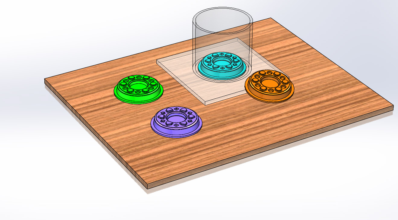 A 3d rendering of the mold and casting set up, with a board, 4 donut components and a cylindrical container