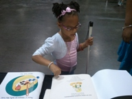 Young Braille Reader checking out a print/braille children's cook book