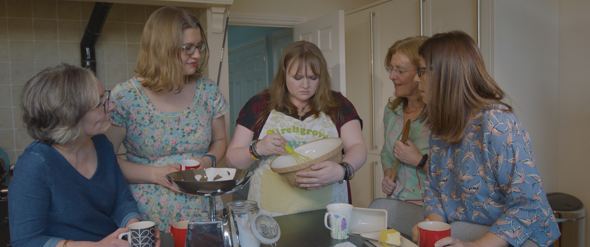 a group of women gather around a central female whisking the contents of a mixing bowl