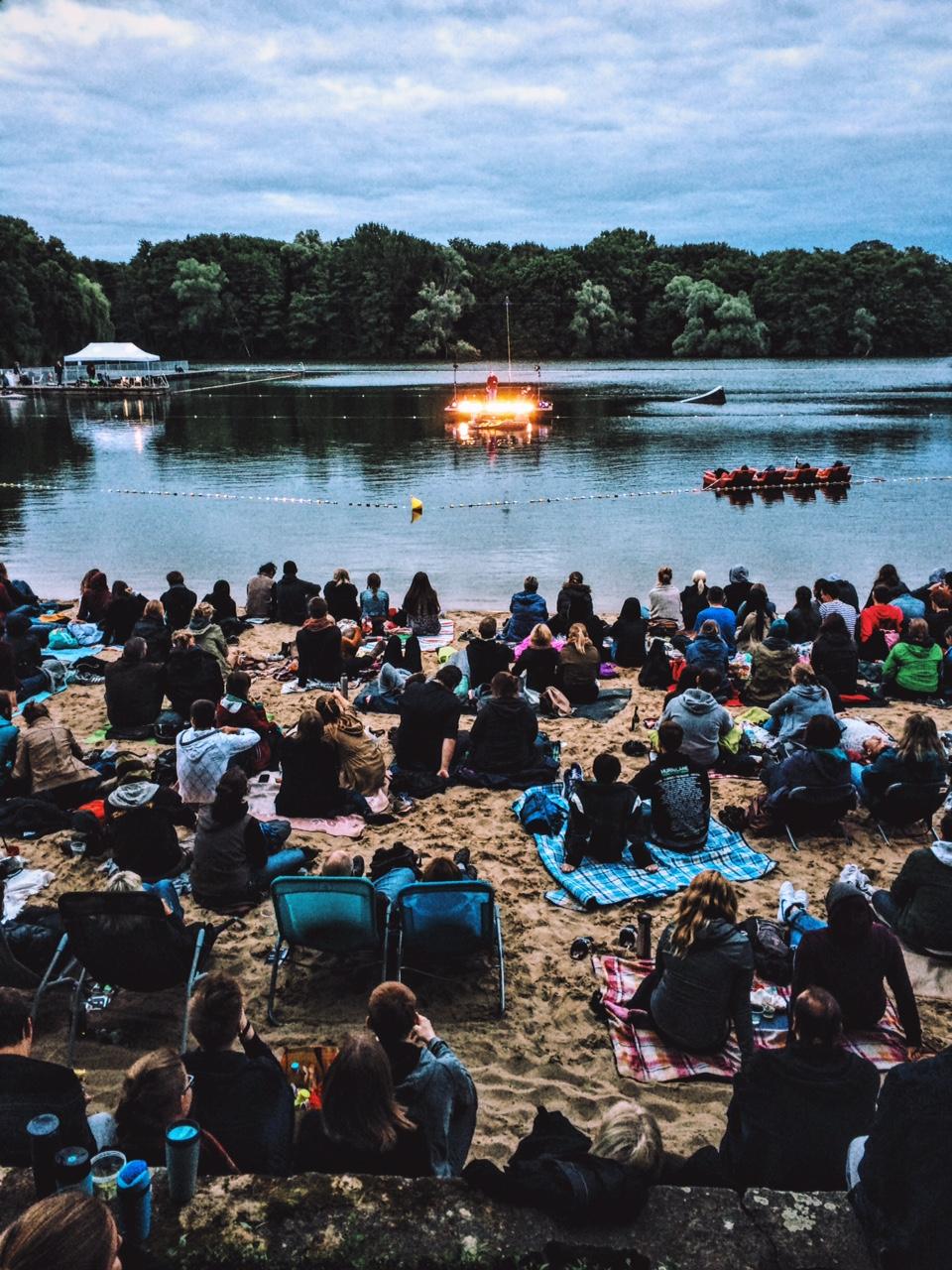 Menschen sitzen am Strand und schauen auf die schwimmende Bühne