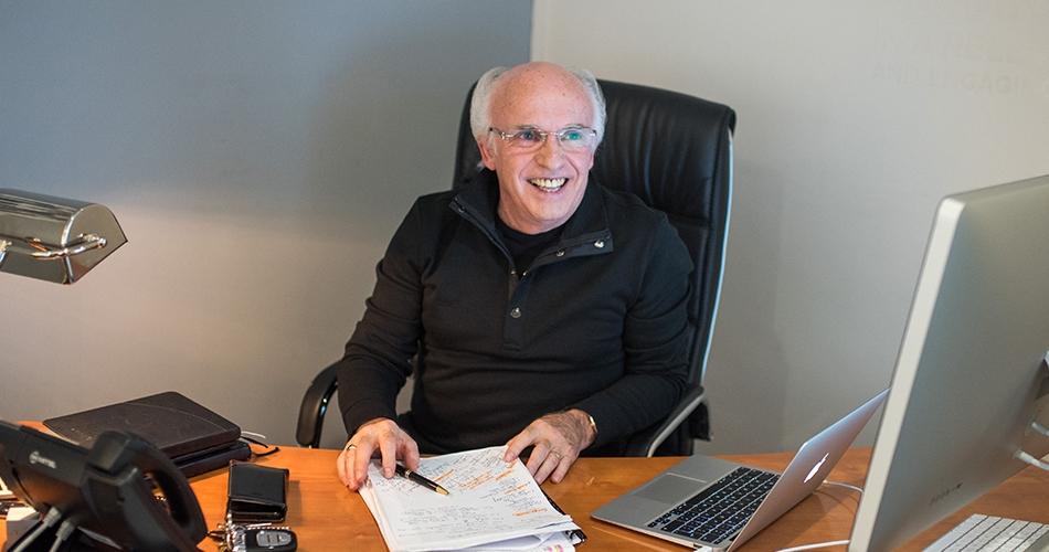 David L'Herroux sitting at his desk