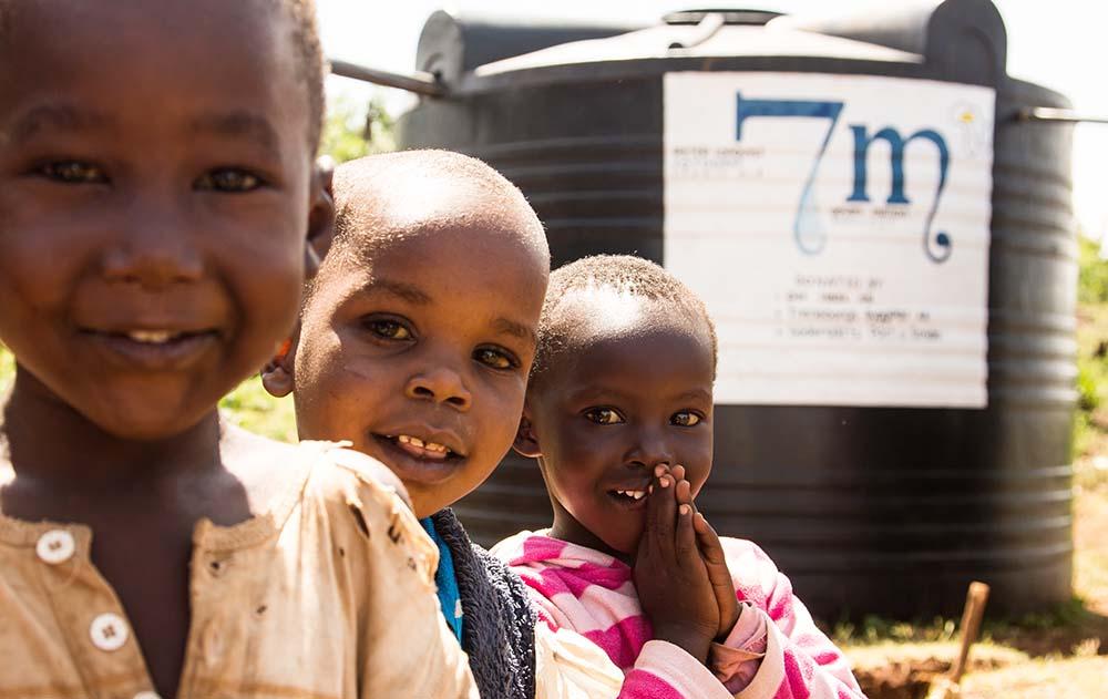 Glada barn framför en vattentank!
