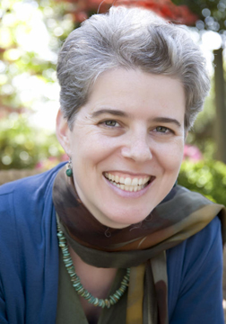 smiling androgynous woman with short gray hair and kind eyes