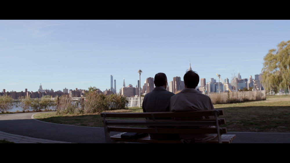 Two men sitting on a park bench looking at a city skyline and sky
