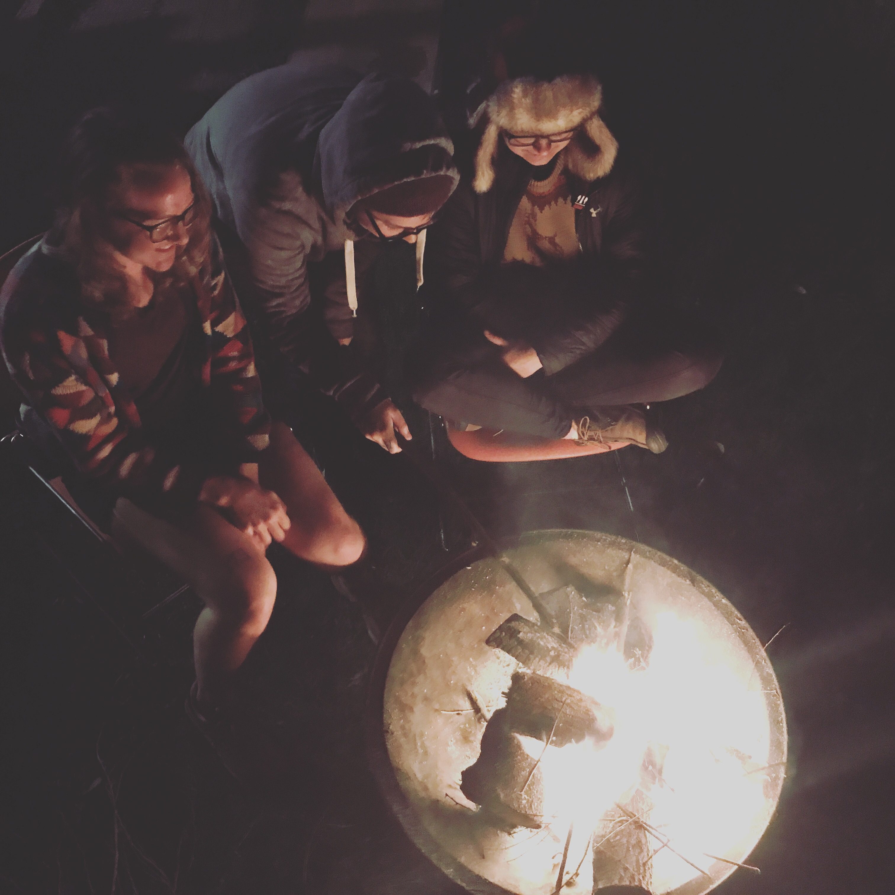 Group of friends gathered around a bonfire