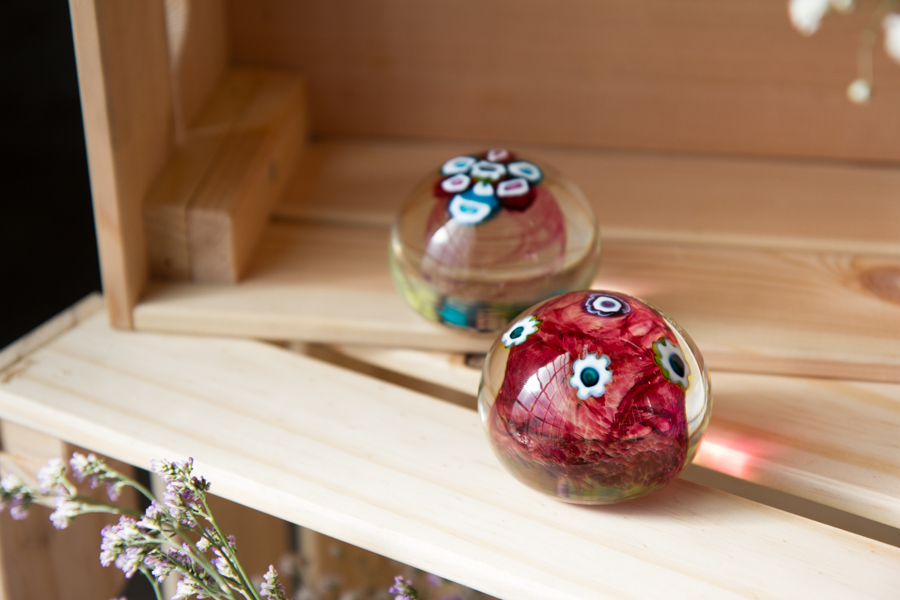 Murrini paperweights sitting on ply crate with flowers around edges
