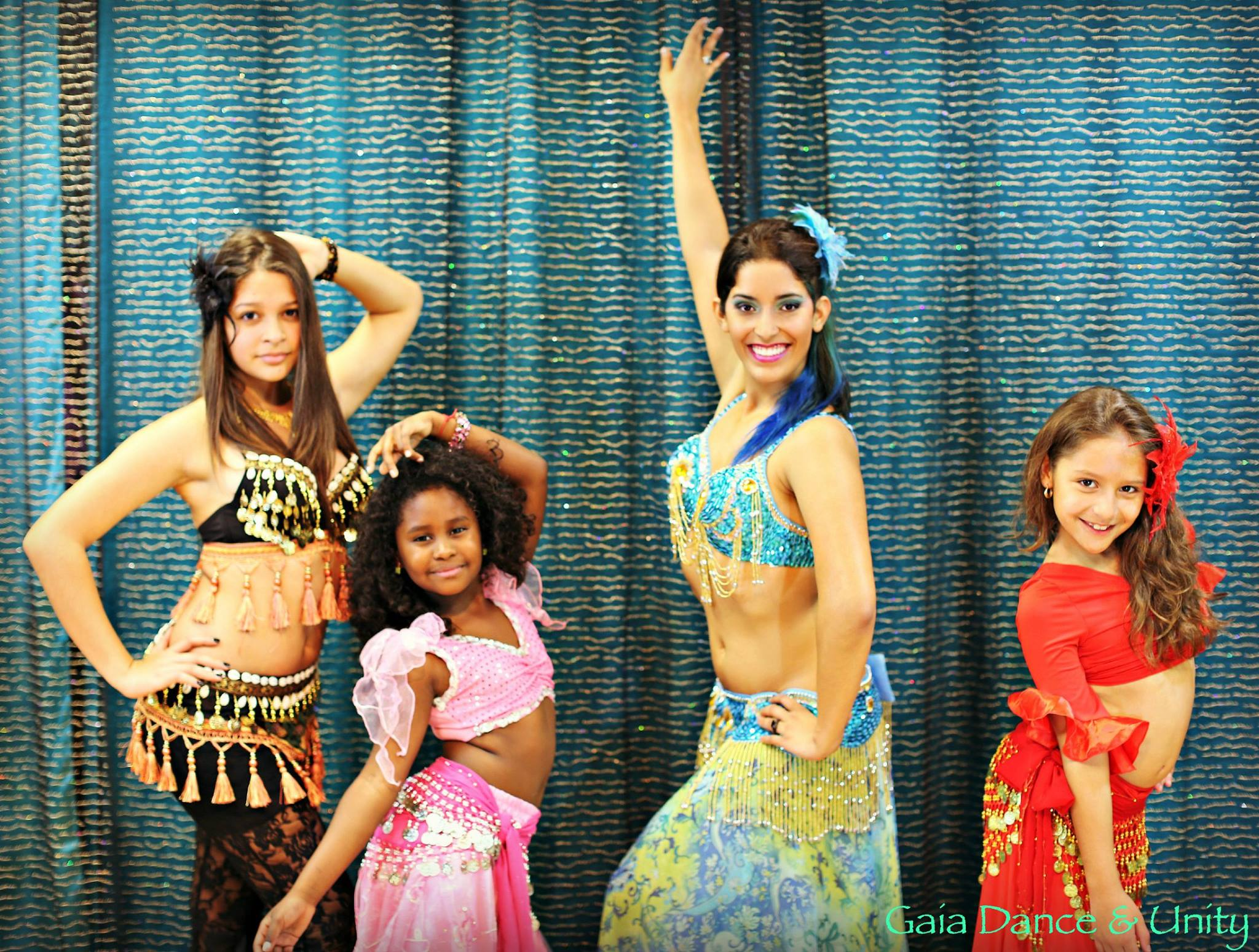 Three children in belly dance costumes posing with their instructor.