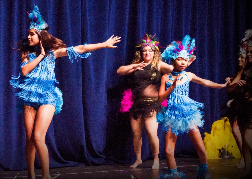 Two kids dancing Brazilian Samba with Adults also dancing in the background. The kids wear bright teal costumes with fringe and little teal and pink feathered headdresses