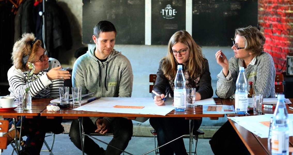 Vier Personen sitzen an einem Tisch und diskutieren angeregt