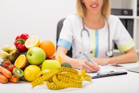 healthcare professional sitting near fruits