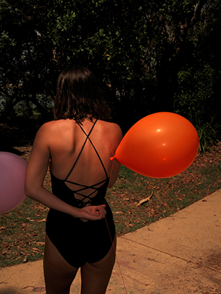 Girl holding a balloon with her back turned to camera