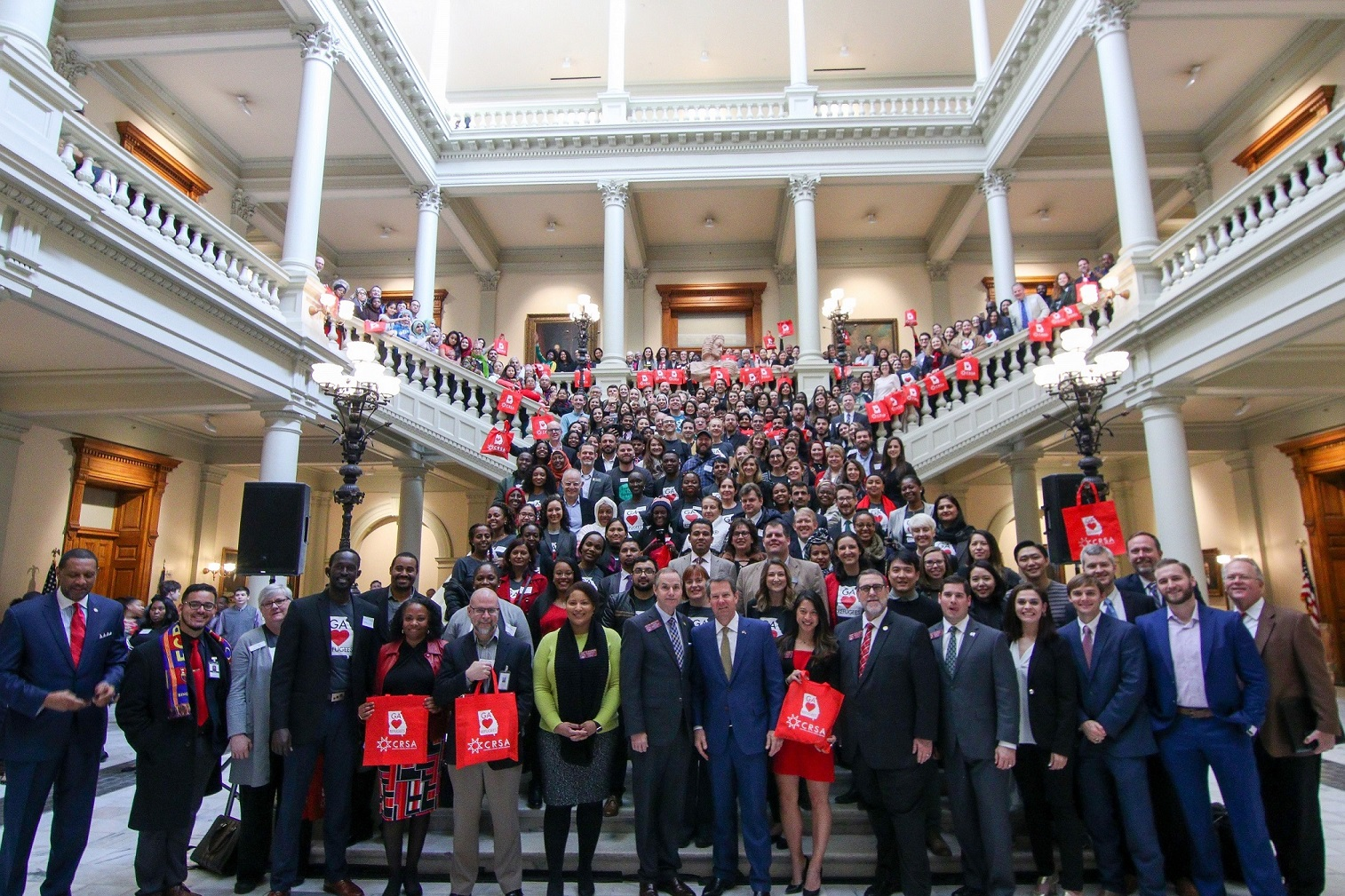 A large marble stairwell in the Georgia State Capitol holds more than 300 people, attendees at last year's New Americans Celebration. Georgia's Governor Brian Kemp stands front and center, will members of the House and Senate and CRSA's leadership.